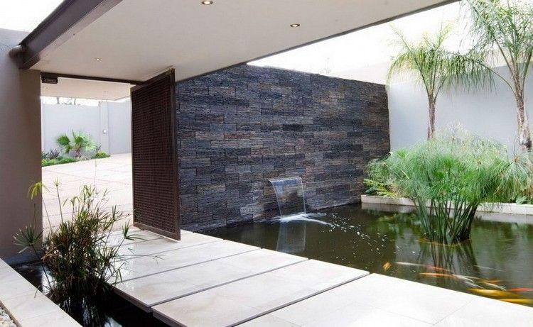 Mur en pierre grise avec cascade intégrée bassin deau plantes aquatiques et