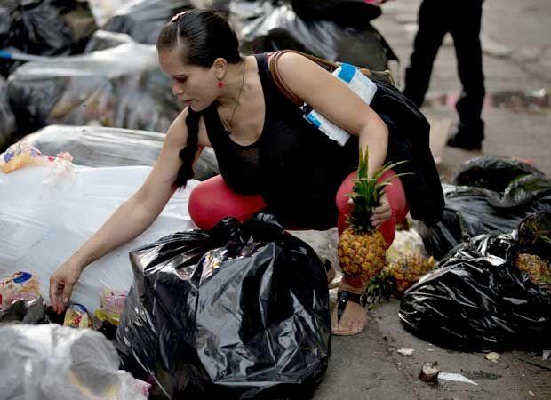 Mulher vasculha sacos de lixo em busca de comida em frente a supermercado de Caracas, Venezuela