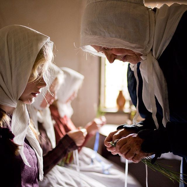 Præsteenken i Eilschous Boliger lærer de unger piger at flette en lavendelparaply. Eilschous boliger lå oprindeligt i Odense og var en enkestiftelse for fattige kvinder, der oprindeligt kom fra velstående hjem. H.C. Andersen var genbo til Eilschous boliger. Den fattige drenge besøgte ofte præsteenken, indtil han rejste til København i 1819. Dette foto er taget af fotograf @thorstenovergaard. #dengamleby #odense #hca #hcandersen #hcafestivals
