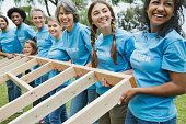 Team of happy volunteers looking away while lifting wooden frame together at park