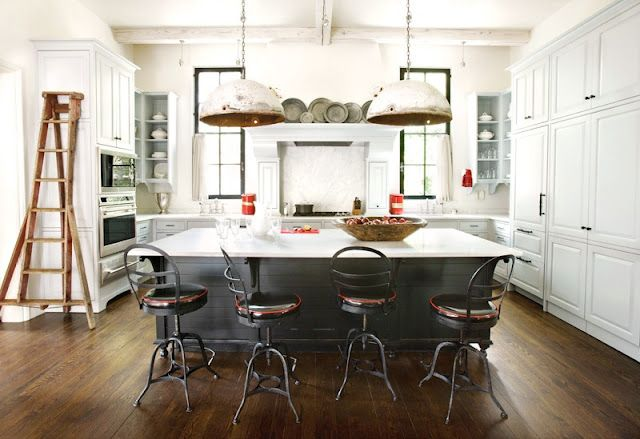 Another dark island with white cabinets. This one belongs to Braves player Derek Lowe, designed by Betty Burgess. I LOVE those windows on either side of the range.