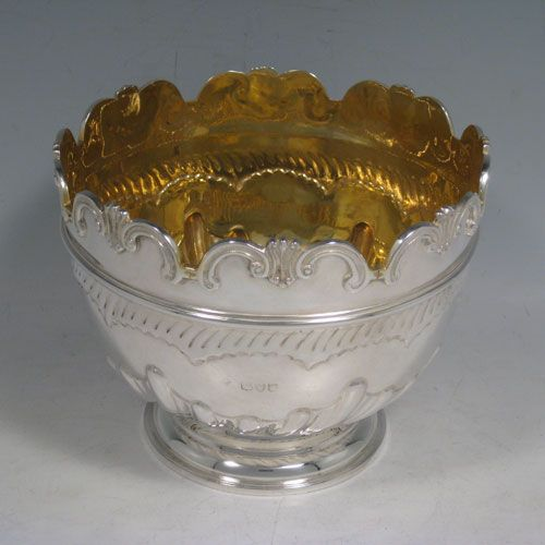Antique Victorian sterling silver Montieth style rose bowl, having a round body with hand-chased swirl half-fluting, an applied reeded band, an applied foliate border, and sitting on a pedestal foot. Made by Charles Stuart Harris of London in 1895. Height 12 cms (4.75 inches), diameter 15 cms (6 inches). Weight approx. 373g (12 troy ounces).