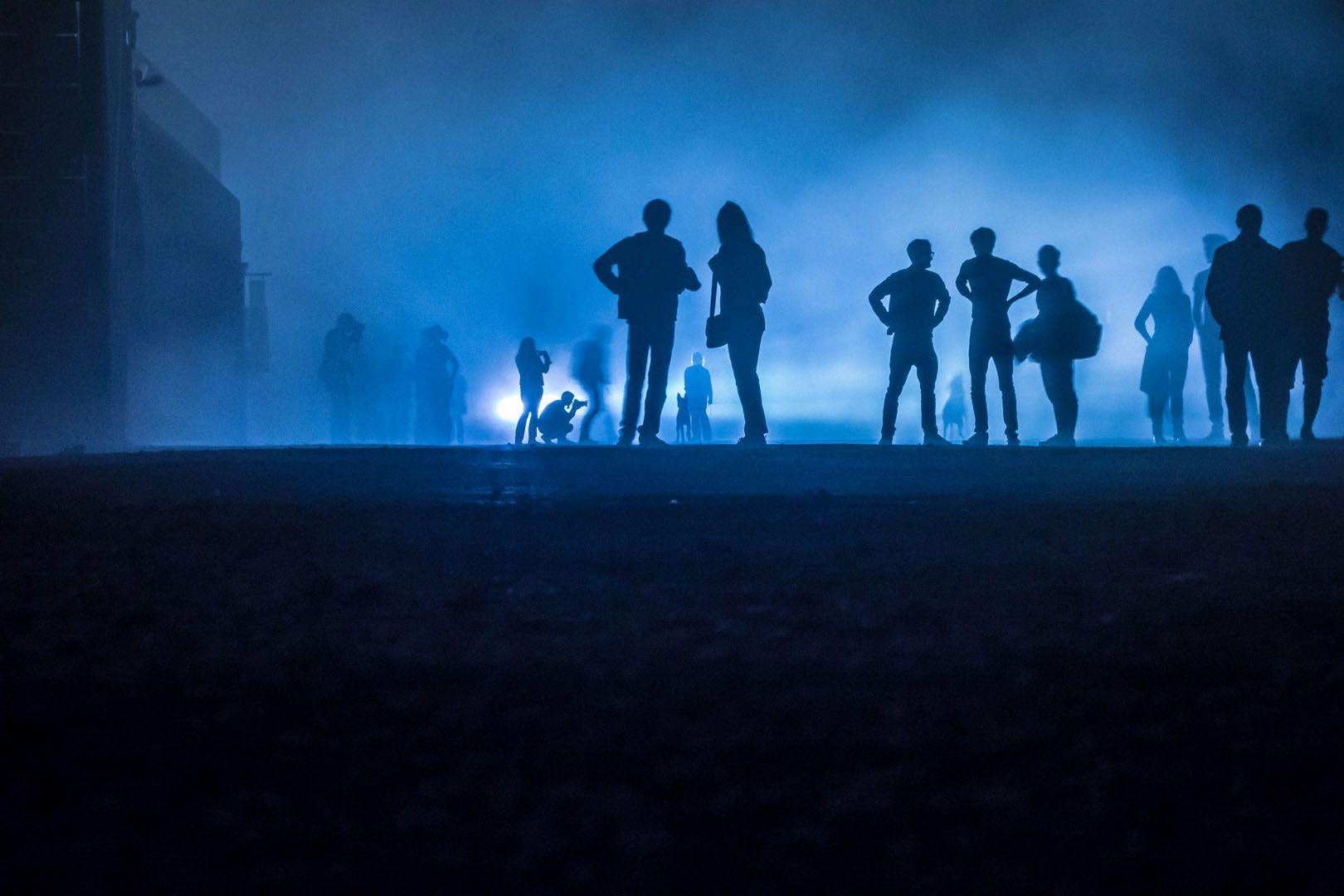 Performance im Nebel 01 – Beunruhigende Performance in Blau: Menschen nachts im Scheinwerferlicht. Hunde bellen. Der Nebel zeichnet in der Tiefe unterschiedliche Schärfen und Tonwerte. 2013, MD | © www.piqt.de | #PIQT