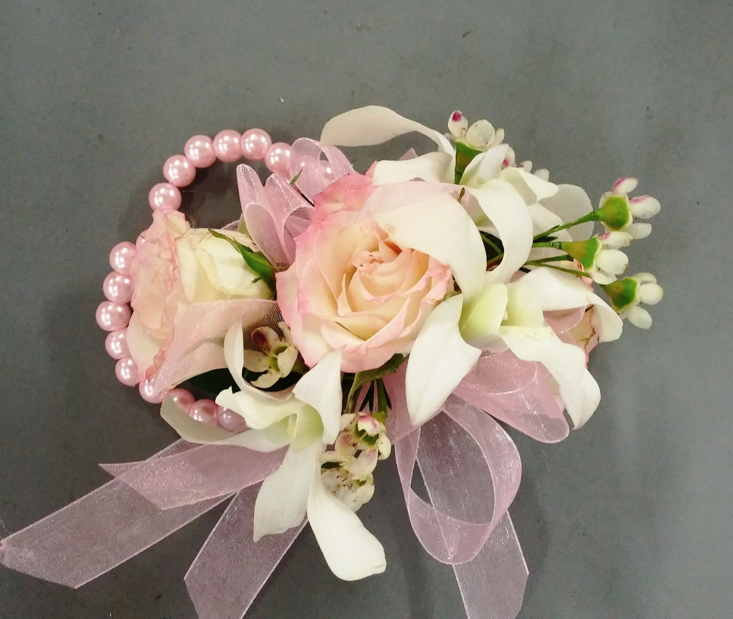 Wrist Corsage With White Orchids And Blush Spray Roses On Light Pink