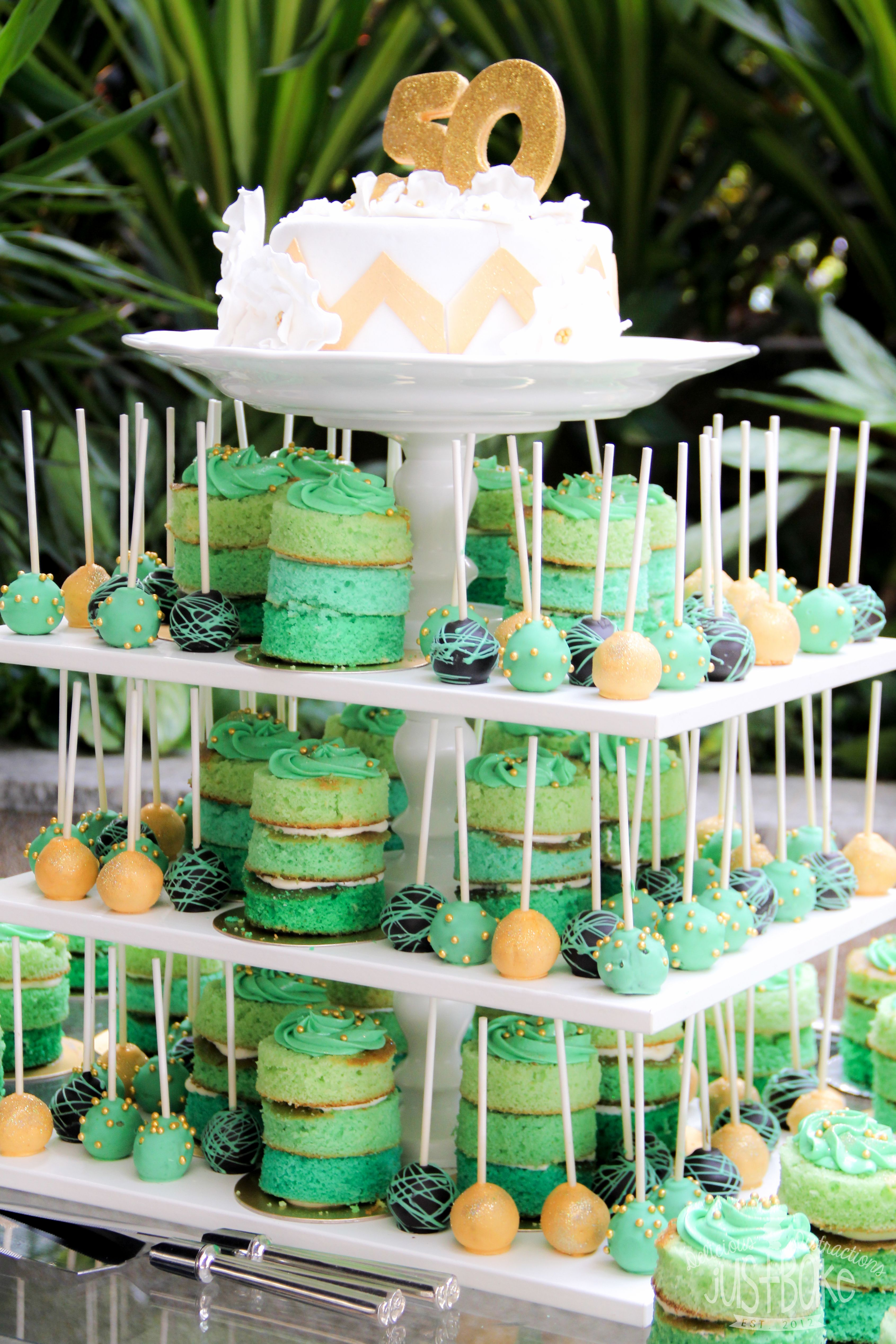A 50th Birthday Party Setup In White Green And Gold Theme Stands Are