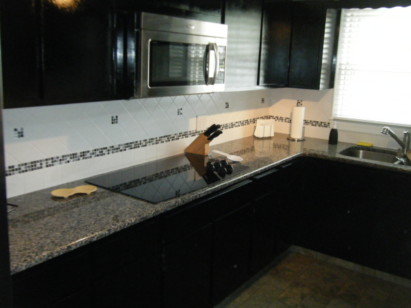 Caledonia Granite Countertops With Custom Tile Backsplash