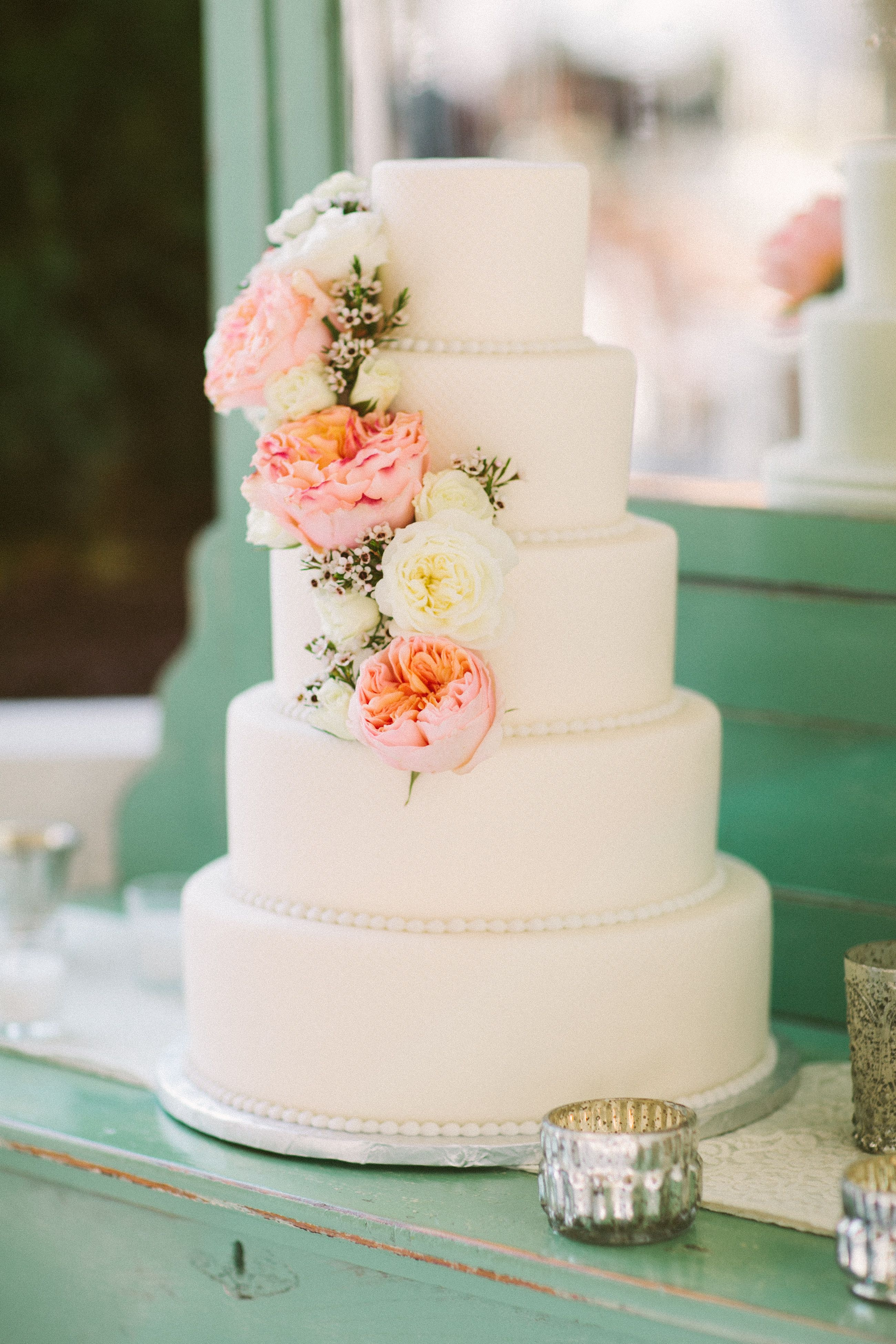 White Cake With Peach Flower Cascade On A Vintage Turquoise Dresser