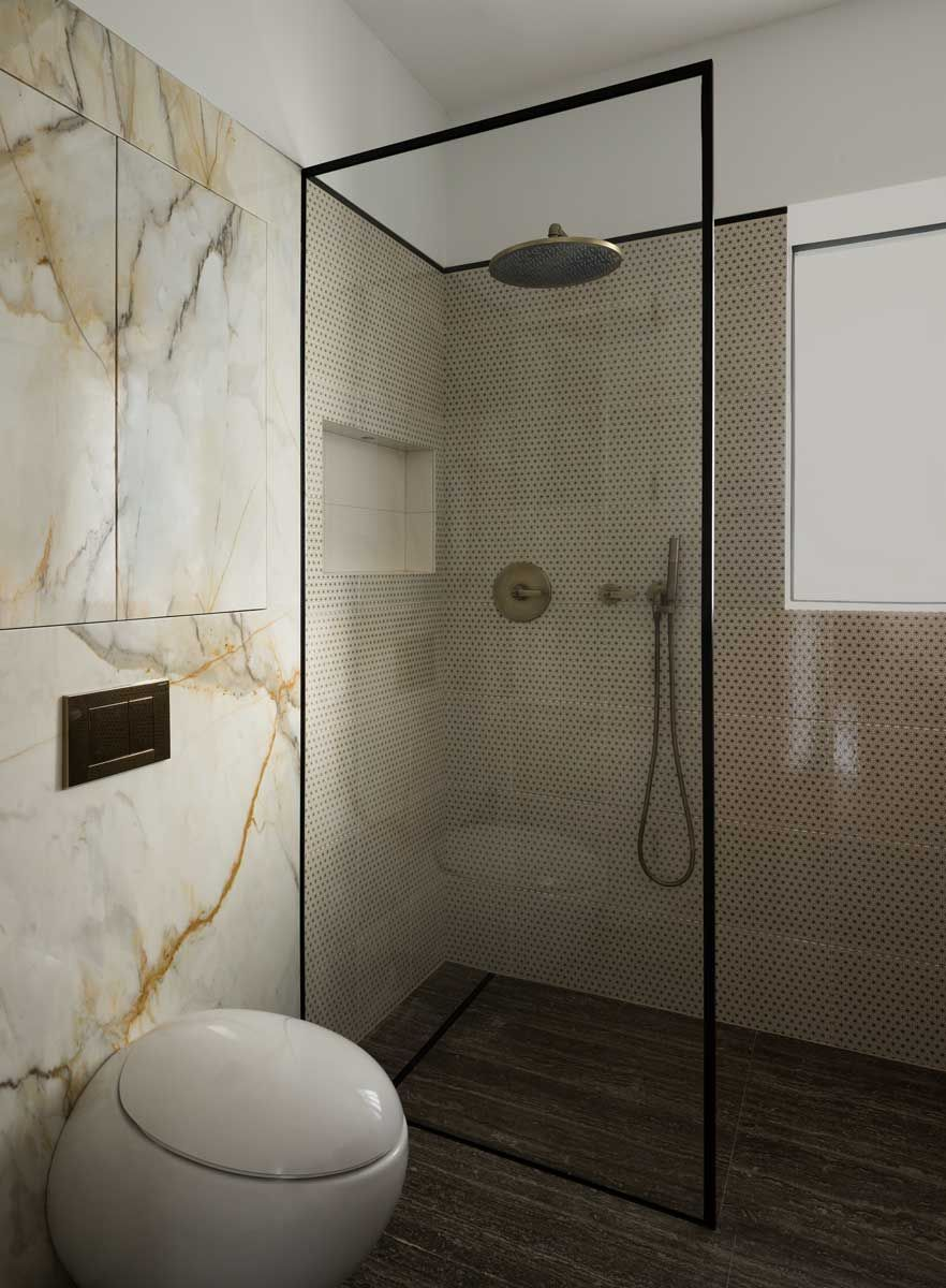 Ensuite Bathroom Fixtures calacatta walls in a guest ensuite bathroom with an elan vital