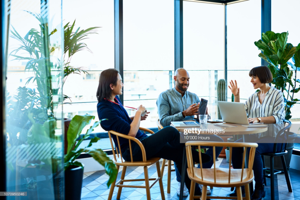 Hispanic businesswoman sitting around table with male