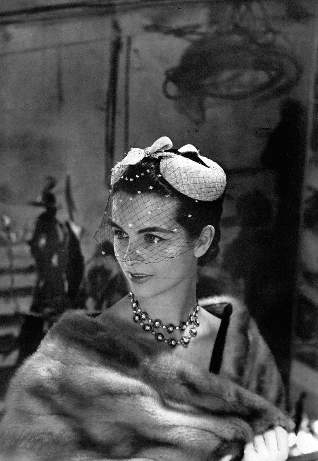 Model is wearing a silver and white lamé evening cap with embroidered voilette by Paulette, photo by Georges Saad, 1955