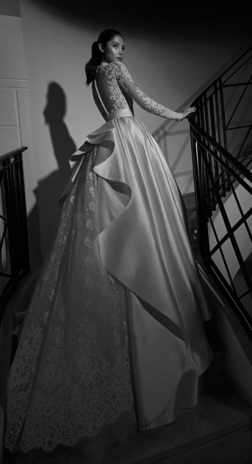 Glamorous long-sleeve lace sleeve wedding dress with dramatic overskirt; Featured Dress: Zuhair Murad