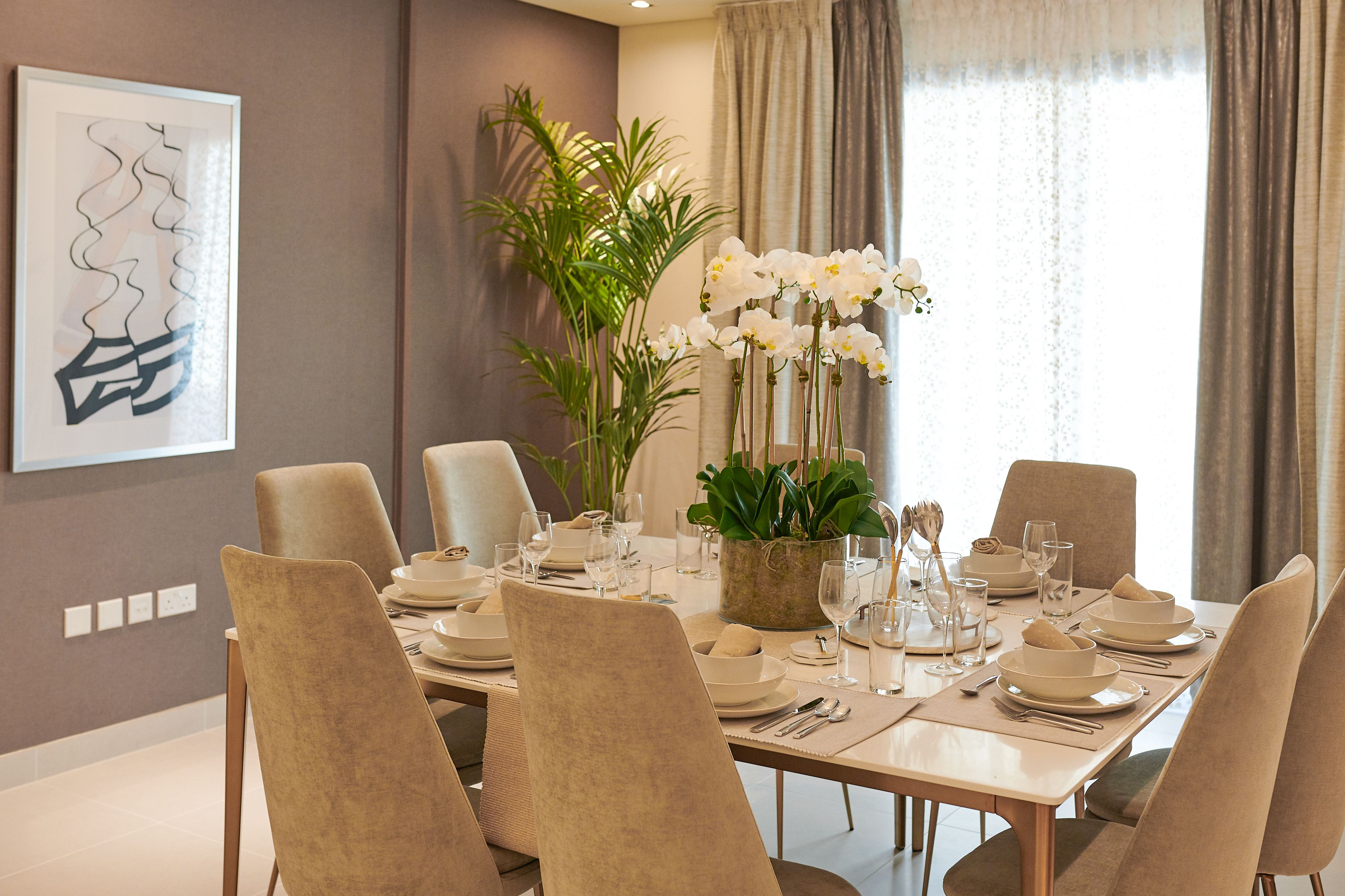 The Cool Sepia Villa by Sarhen International used plants as a fresh accent in this copper and grey formal dining room. #interiordesign #homedecor #diningroomdesign #diningtabledecor