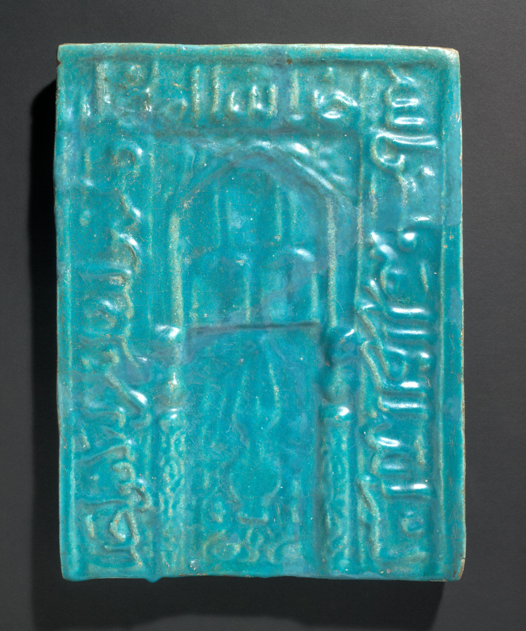 Plaque with mihrab motif framed by inscription in relief