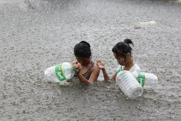 Residents wade through a flooded street to buy drinking water during heavy downpour in Malabon, Metro Manila August 1, 2012. Typhoon Saola (Gener) is likely to stay in Philippine territory until Friday, the Philippine Atmospheric Geophysical and Astronomical Services Administration (PAGASA) said on Wednesday, and the National Disaster Risk and Reduction Council said the death toll from Gener stood at 12