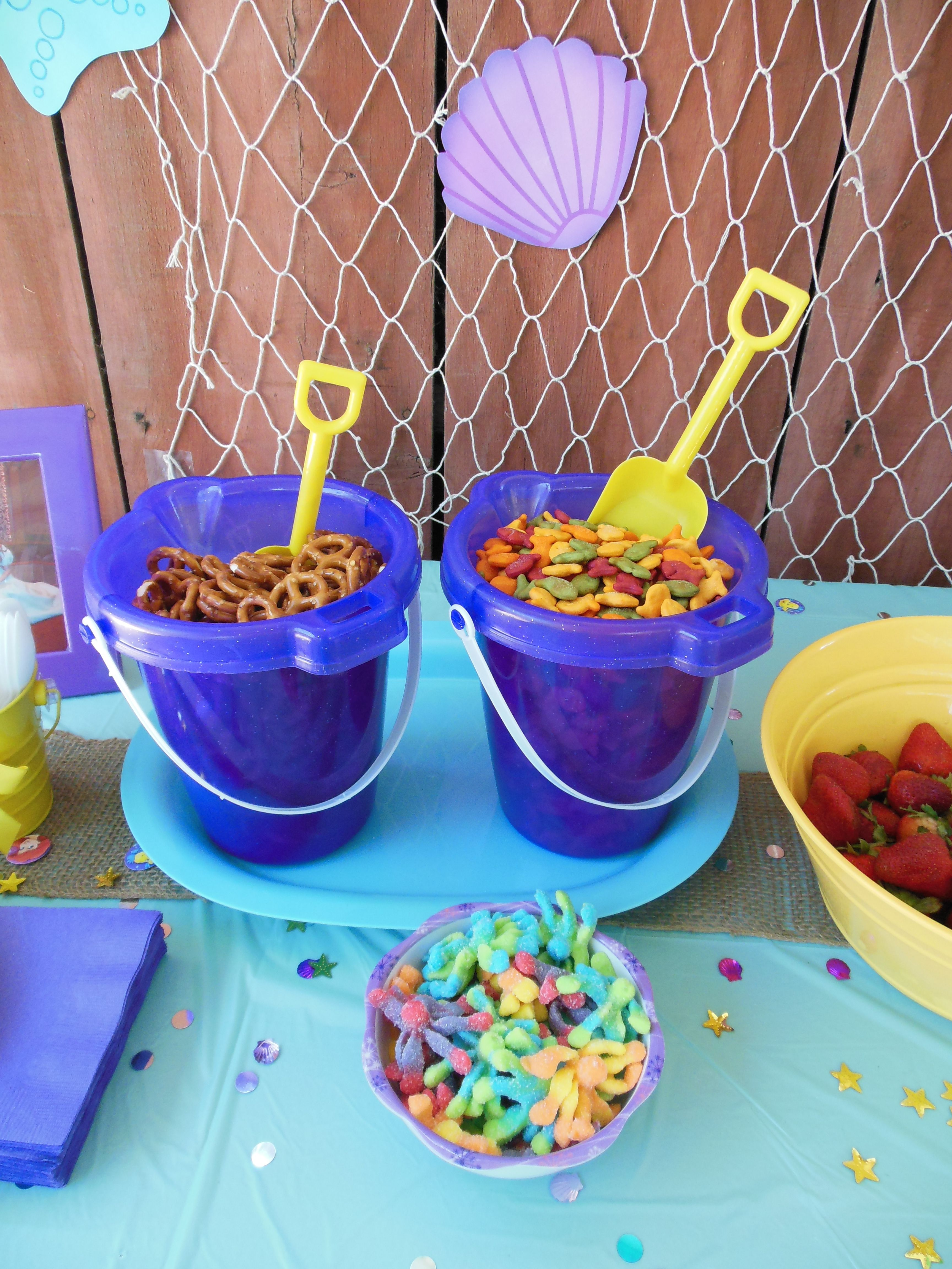Beach party table decorations ocean party snacks out of a sand pail  quinnus bday  pinterest