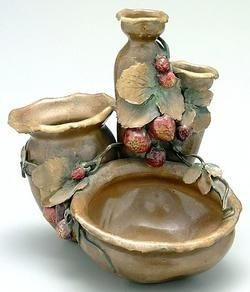 pottery & porcelain, Austria, A Teplitz Amphora vase having four joined bowl forms with berries and leaves in full relief, glaze with gilt highlights, base marked Amphora with impressed numbers.