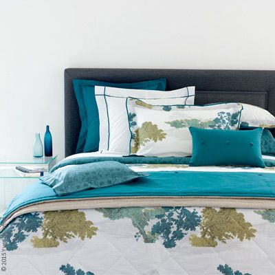 Calicot by Yves Delorme combines brightly printed floral designs on a white background and a small, dark and repeating floral motif on a peacock-colored background. White background shams and duvet cover are outlined with peacock piping. Sheets and shams with peacock background compliment and contrast superbly.