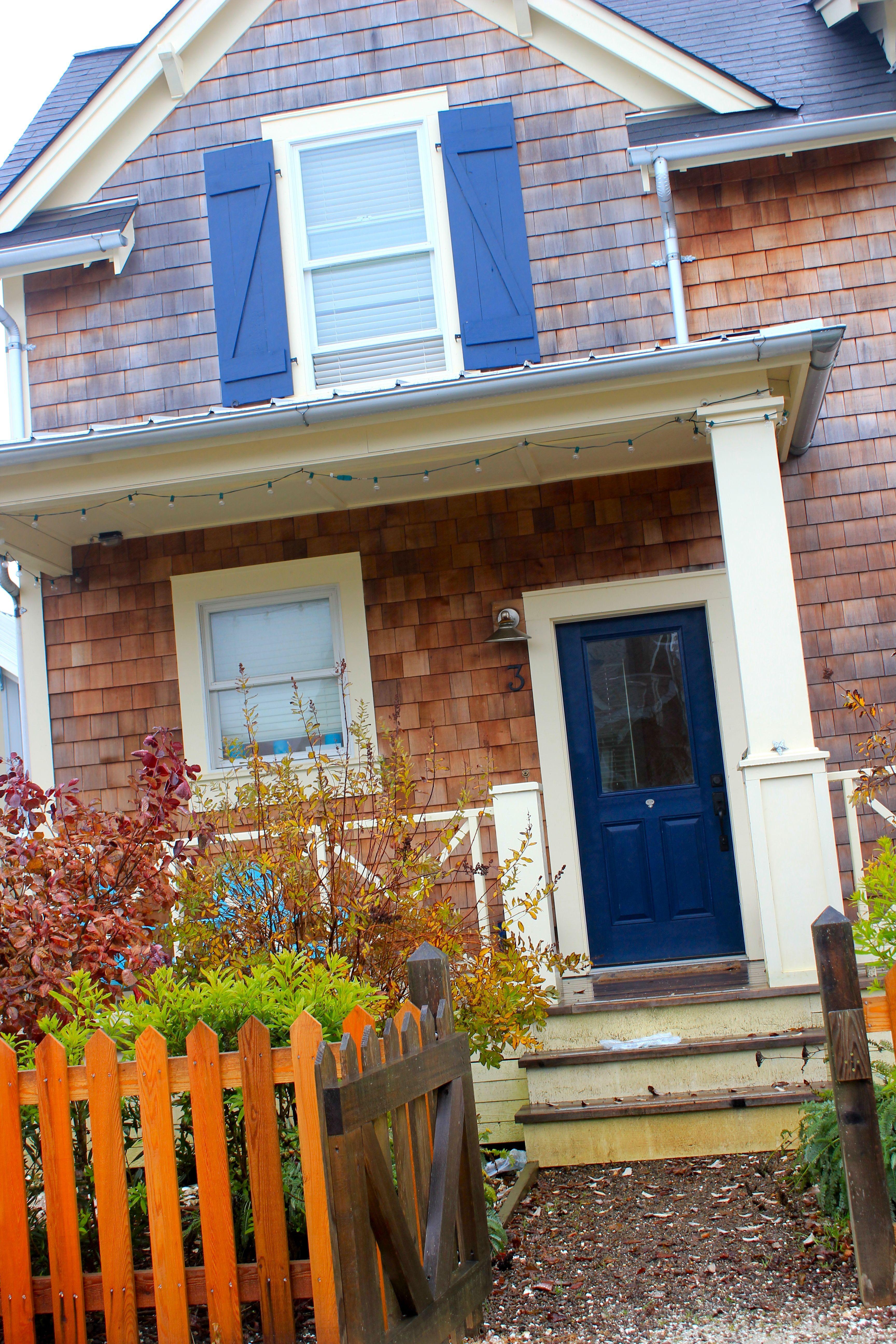 Cute porch light brown shingle siding navy blue for Beach house siding ideas