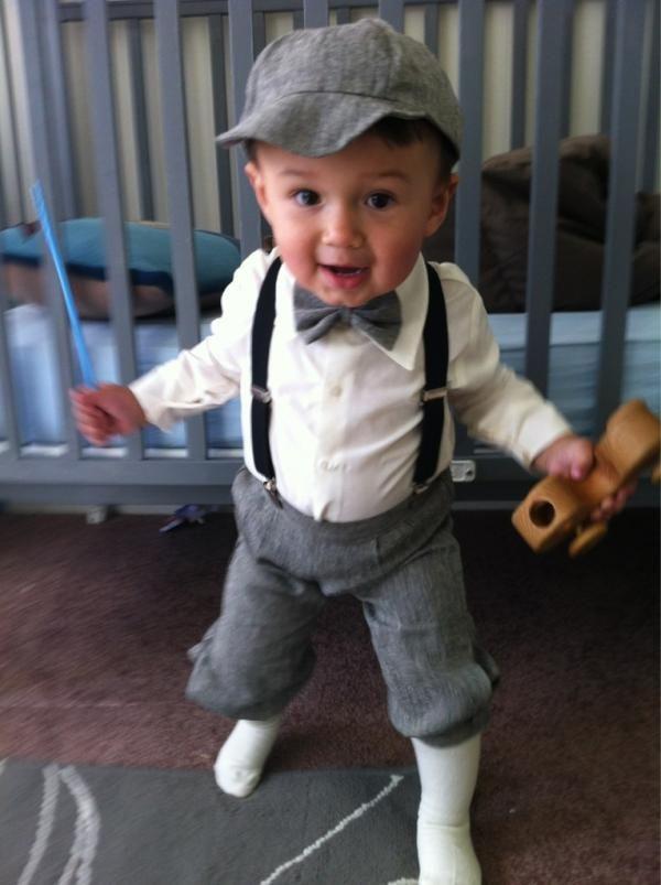 El  chico lleva una camisa blanca, y pantalones grises, y calcetines blancos, y la gorra gris.