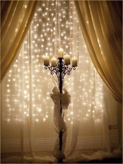 An Enchanting Look Fairy Lights Behind A Sheer Curtain With Lit Candles On Candle Stand In Front Could Be Used At Wedding Ceremony Reception Or For