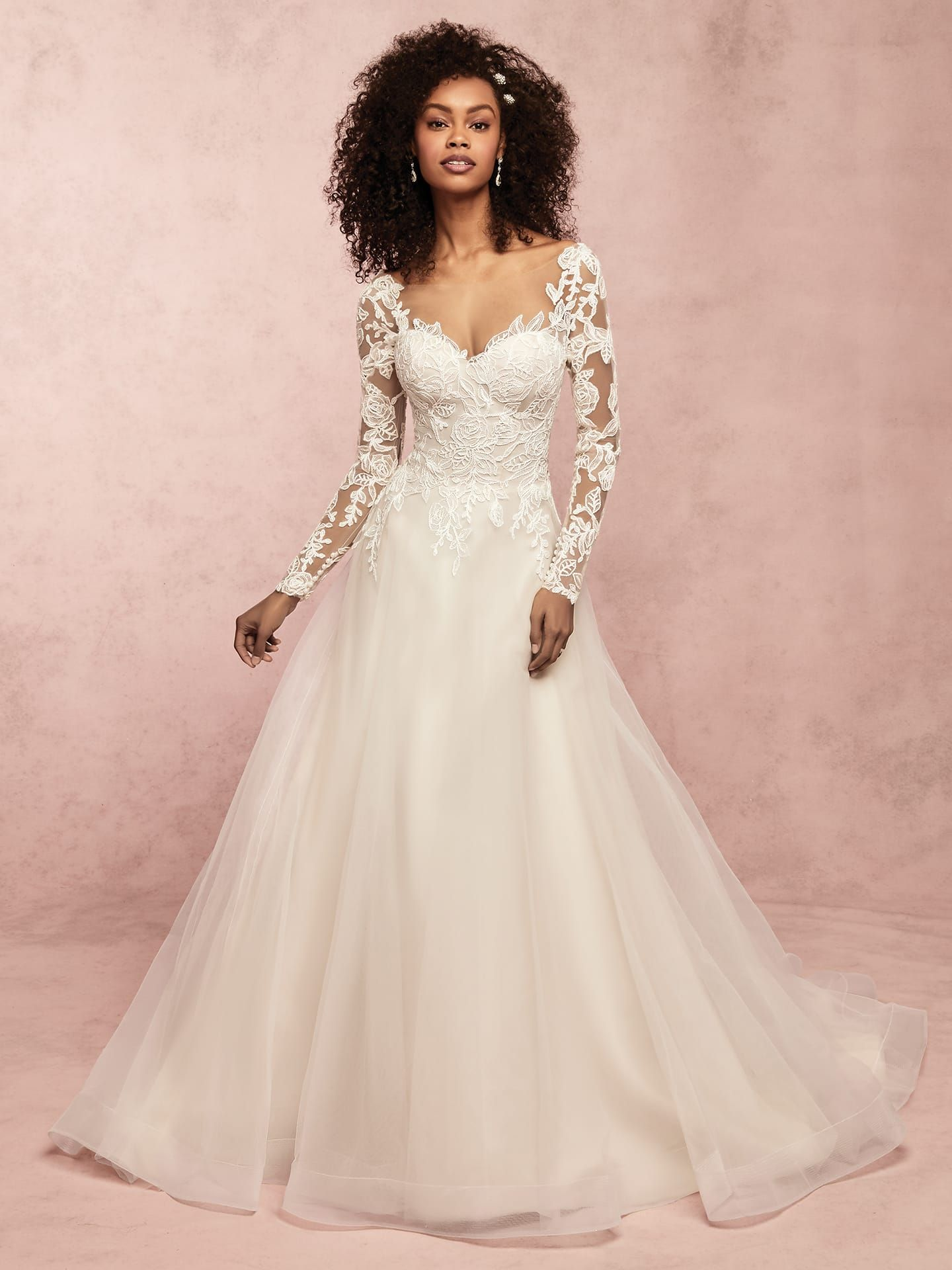 Unique floral lace motifs dance over the bodice of this