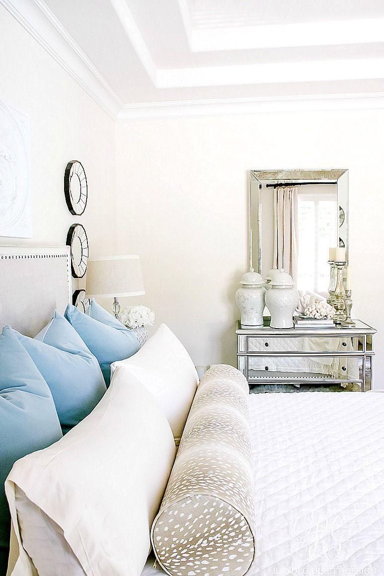 white master bedroom with blue velvet pillows and antelope bolster