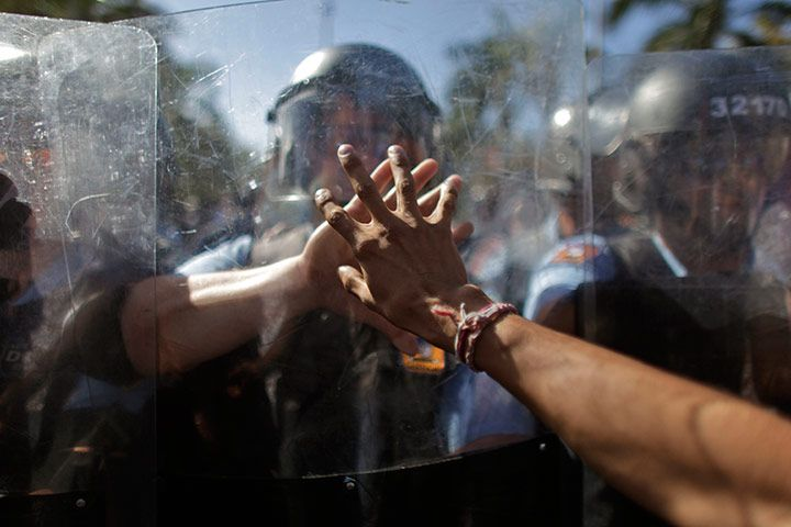 San Juan, Puerto Rico: A protester touches the shield of a riot police officer