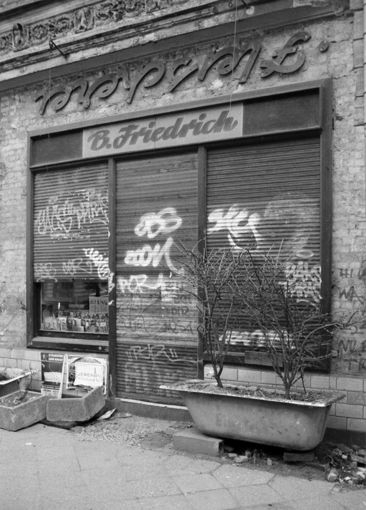 """Tucholskystraße in Mitte, 1996 Die Comicbibliothek Renate mit dem kopfstehenden Schriftzug """"Fleischerei"""". Das Haus wurde von 1998-2002 saniert, der Schriftzug verschwand, aber die Bibliothek ist noch da. The comic library Renate with the advertising inscription 'Fleischerei' (butcher shop) upside down. The building was renovated from 1998-2002, the inscription disappeared, but the library is still there."""