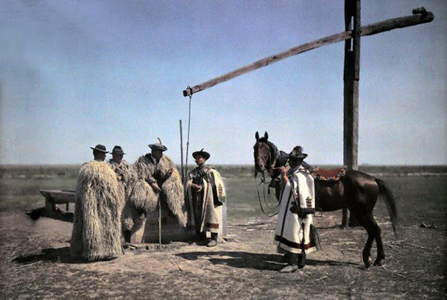 1932, Hungary --- Cowboys in sheepskin and a horse center around a well in the PUSZTA -Hortobagy , Hungary --