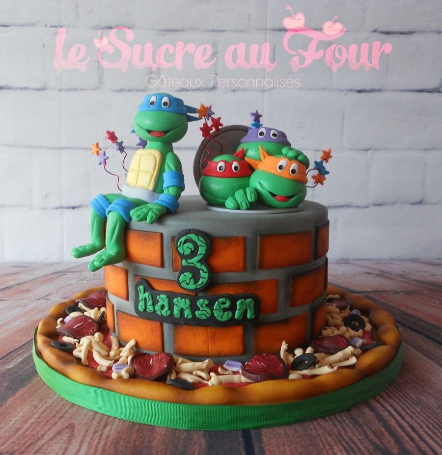 Tmnt Cake The Teenage Mutant Ninja Turtles Are Back This Two Tiered Cake Is Covered In Fondant With The Four Turtles Coming Ou Cake Tmnt Cake Cake Creations