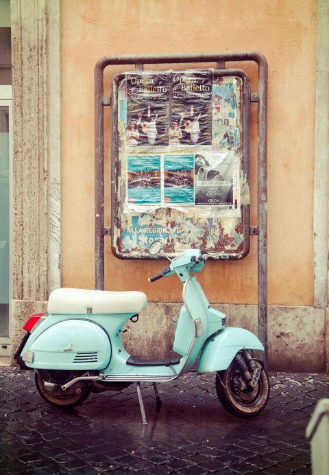A Vespa parked at a café near the Colosseum.