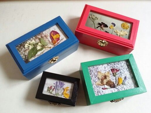 Cajas de madera pintadas en diferentes colores con flores naturales ...