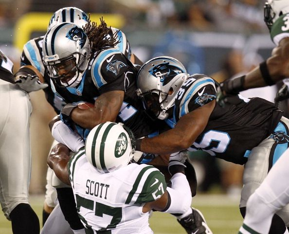 DeAngelo Williams #34 of the Carolina Panthers tries to break free of Bart Scott #57 of the New York Jets during their preseason game at MetLife Stadium on August 26, 2012 in East Rutherford, New Jersey. (Photo by Jeff Zelevansky/Getty Images)