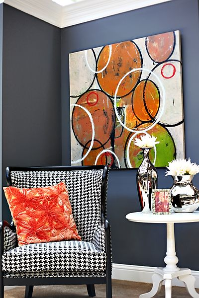 black & white houndstooth chair, charcoal walls, and abstract art.