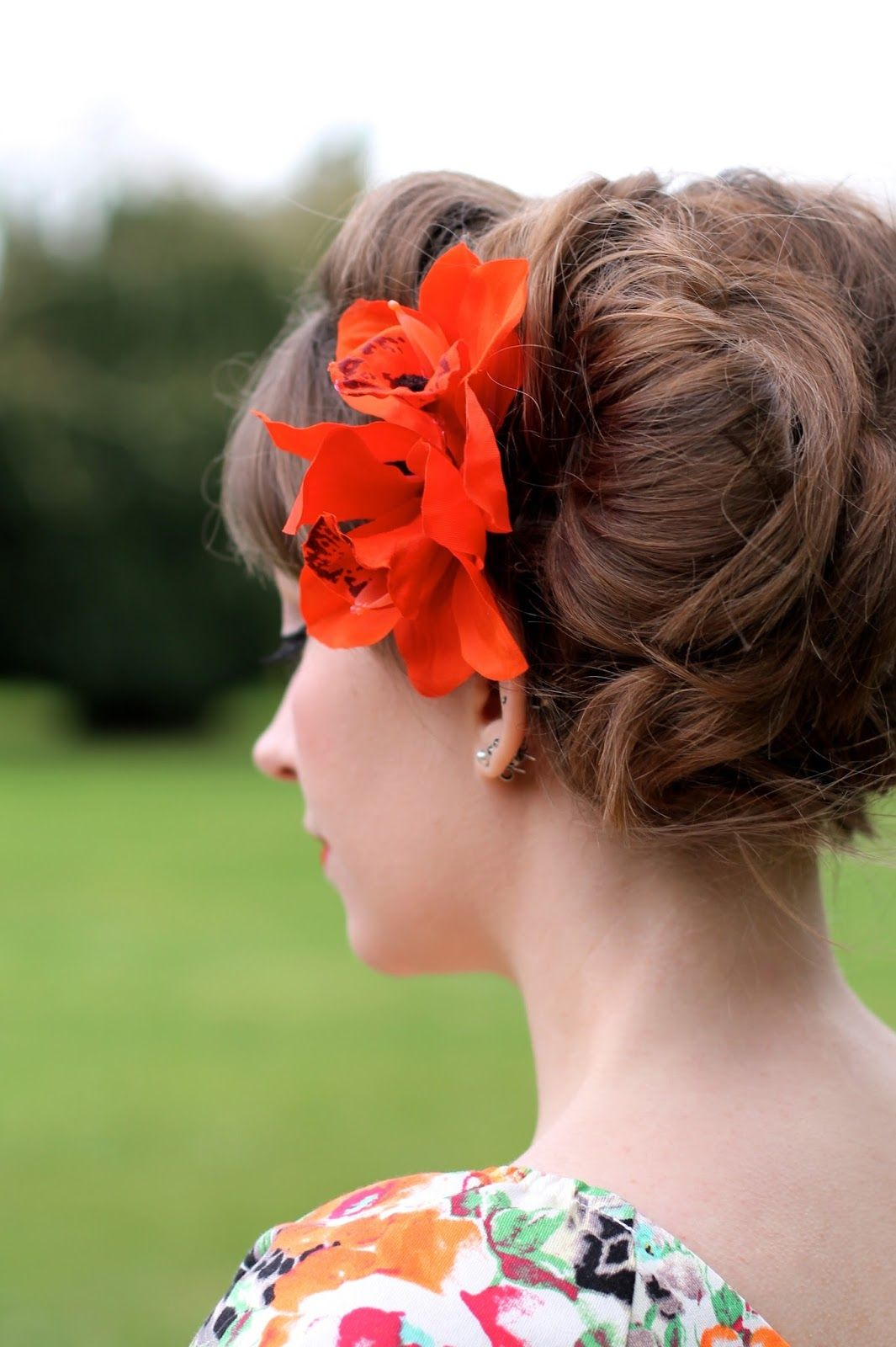 messy side bun with orange orchid hair flowers | hair | pinterest