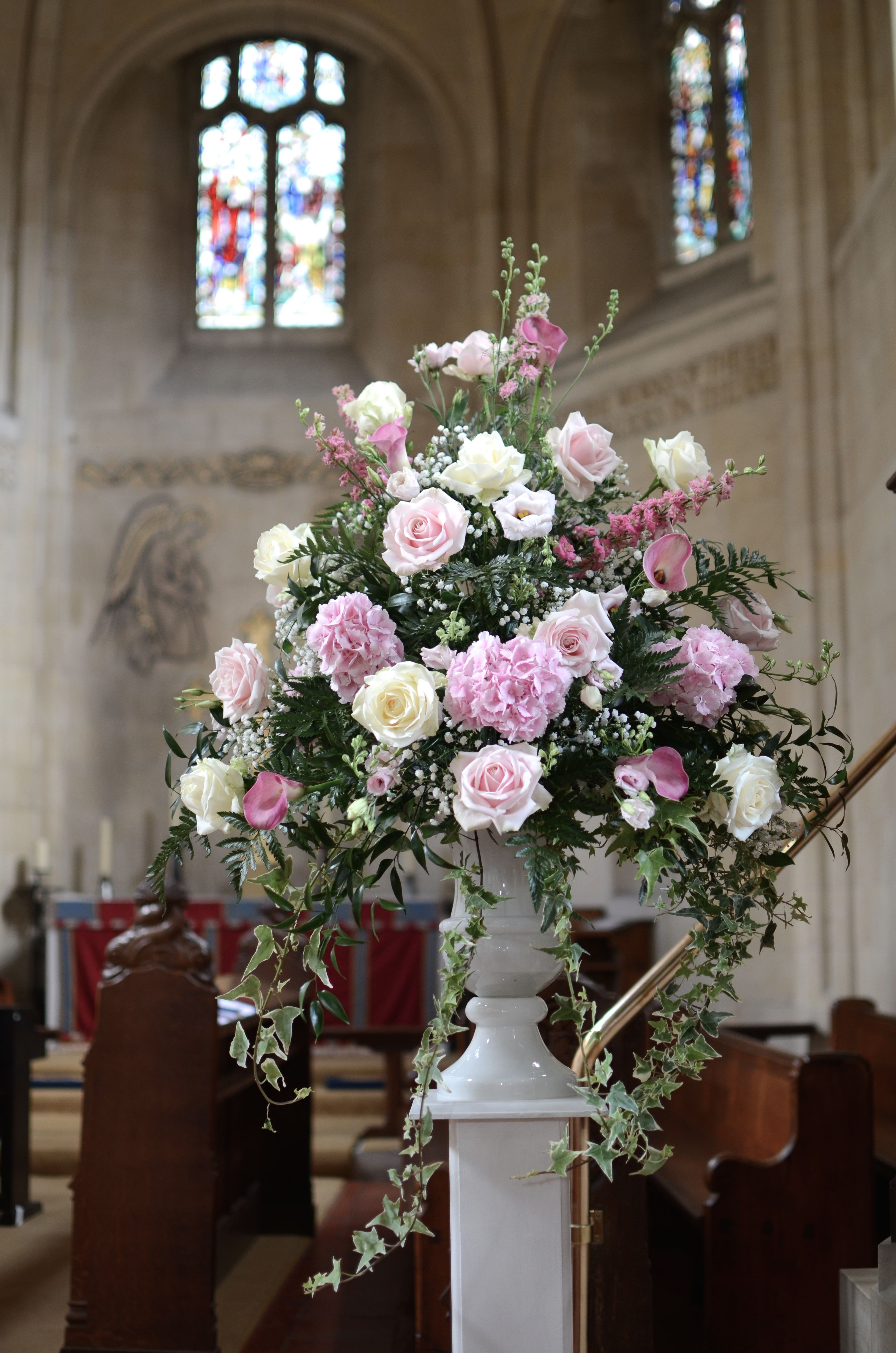 Traditional Pedestal Arrangement In Shades Of Pink In A White Urn