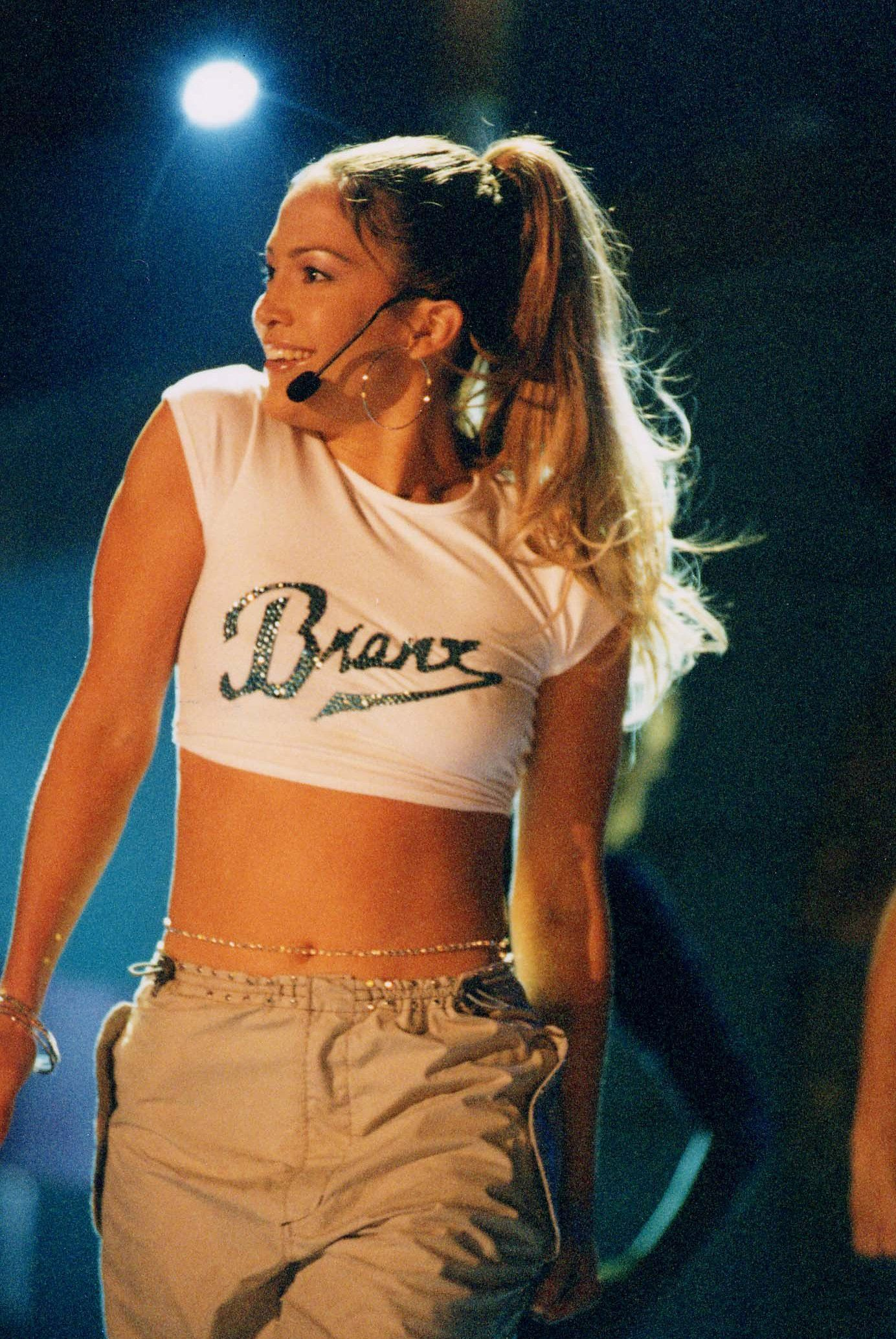 "April 13, 2000 - It's all about Jenny From the Block with low-slung cargos and a ""Bronx""-emblazoned crop top—complete with a pair of oversize hoops."
