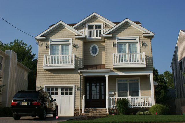 Elevation, Tan / Beige Siding, White Trim, Balconies, Covered Front Porch, Oval Window, Stone Steps, Wood Entry Door