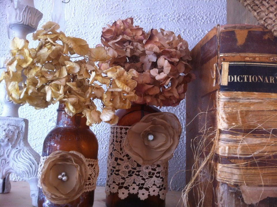 Vintage bottles adorned with vintage lace and fabric flowers at House of Envy Boutique.