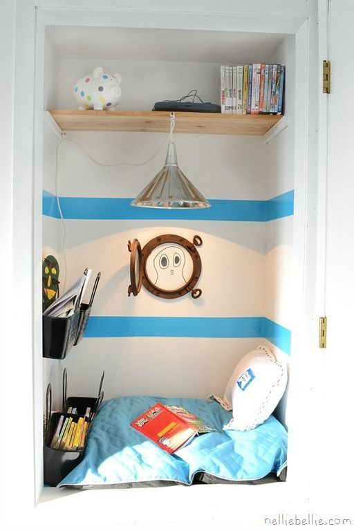 sweet little reading nook made out of  closet - love the porthole!