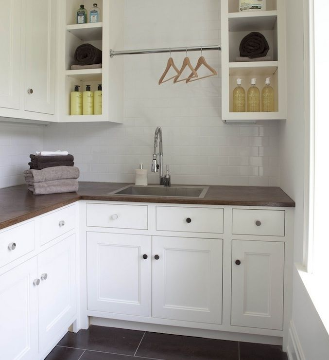 Modern sleek laundry room with white cabinets with butcher block