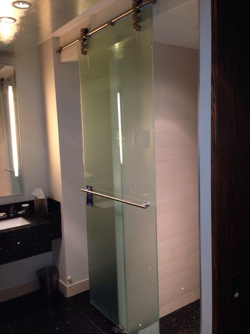 Sliding glass door on metal rollers between toilet & shower stalls ...