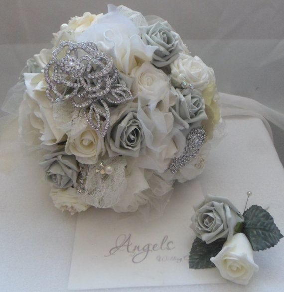 Soft ivory and silver grey roses, with tulle, lace ,diamante and pearls. Finished with 2 statement brooches, silver flower and feather . Handle
