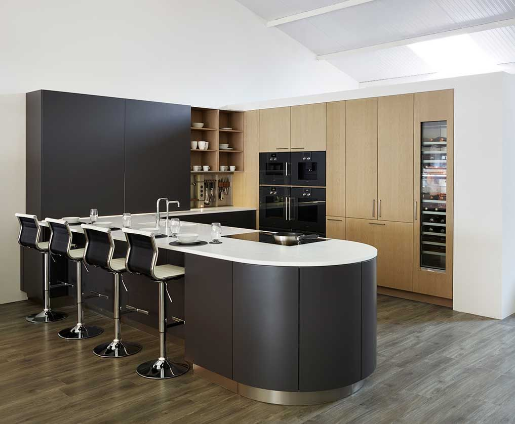 Snug Kitchens Newbury Pronorm Pro-Line Kitchen with sliding doors, and a curved peninsula breakfast bar, in Matt Stratus Grey with Clay Oak Veneer and Glacier White Corian worktop.