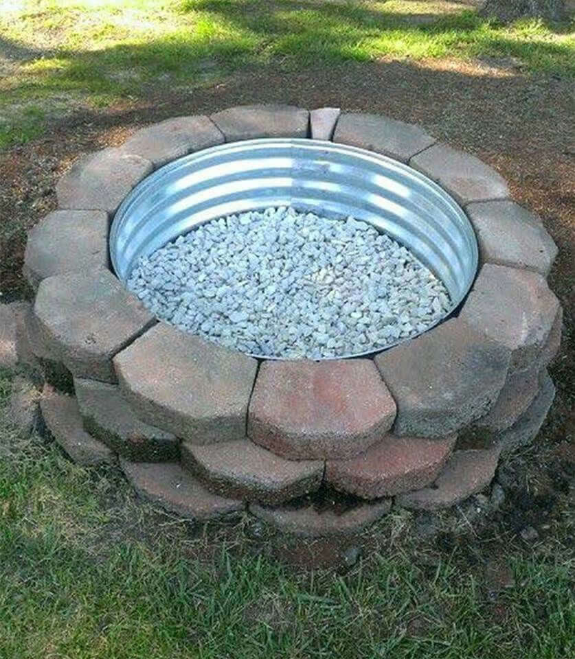 nice idea for a fire pit  using metal ring  stones and landscaping blocks