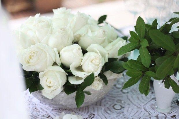 Arranjo de rosas brancas no floral úmido com folhas verdes.