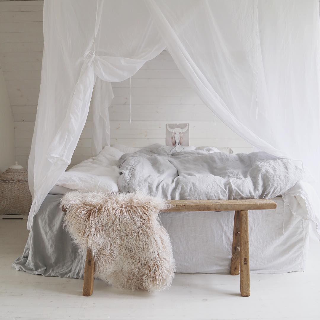une chambre avec lit baldaquin banc en bois et peau de. Black Bedroom Furniture Sets. Home Design Ideas