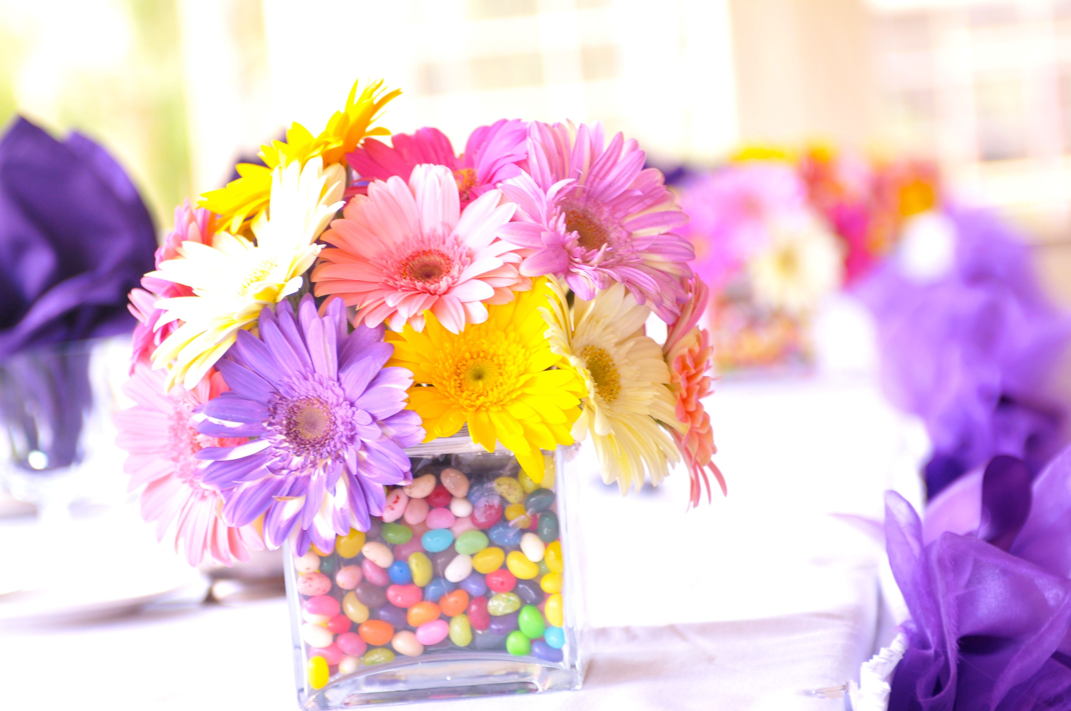 Gerber daisy centerpiece with jelly beans. How cool...then people ...