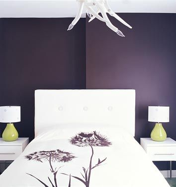 Deep purple accent wall adds drama while the white headboard and linens  keeps the room light. Deep purple accent wall adds drama while the white headboard and