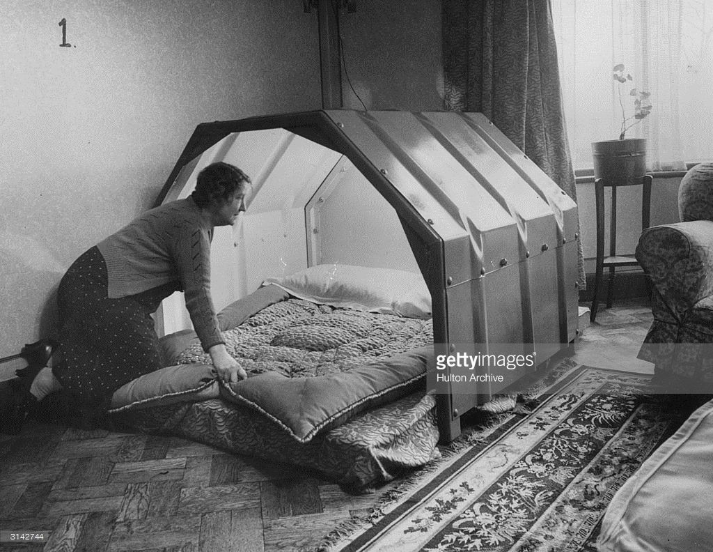 a woman makes the bed in an indoor bomb shelter 1940 ww2 air